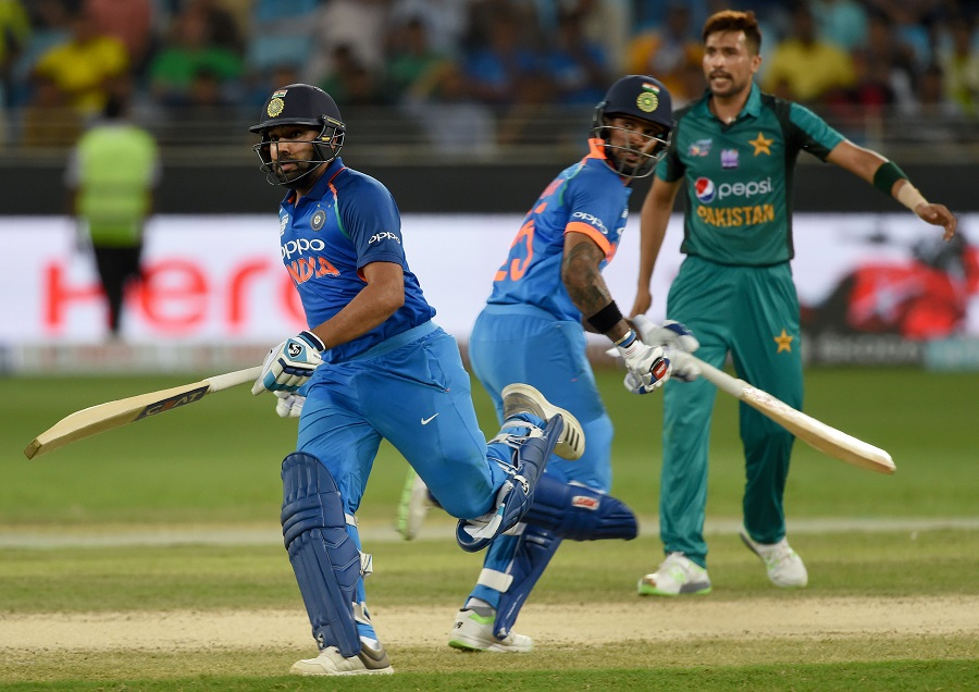 Indian cricket team captain Rohit Sharma (L) and Shikhar Dhawan runs between the wickets as  Pakistan cricketer Mohammad Amir (R) looks on. PHOTO: AFP