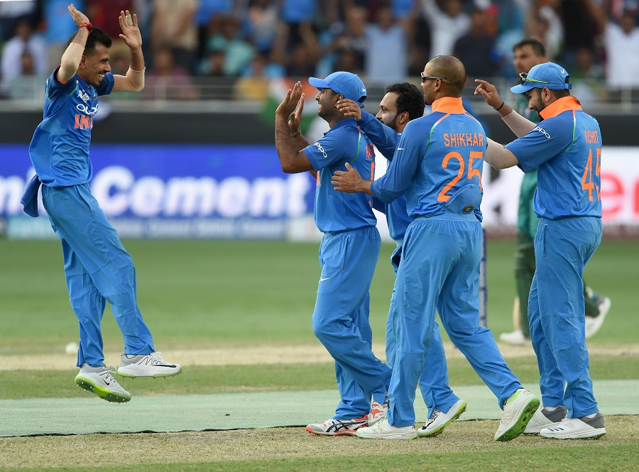 Indian cricketer Yuzvendra Chahal (L) celebrates with teammate after dismissing Pakistan batsman Shoaib Malik. PHOTO: AFP