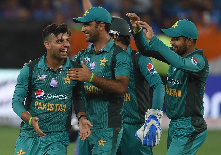 Pakistan cricketer Shadab Khan (L) celebrates with teammates after he dismissed unseen Indian cricket team captain Rohit Sharma. PHOTO: AFP