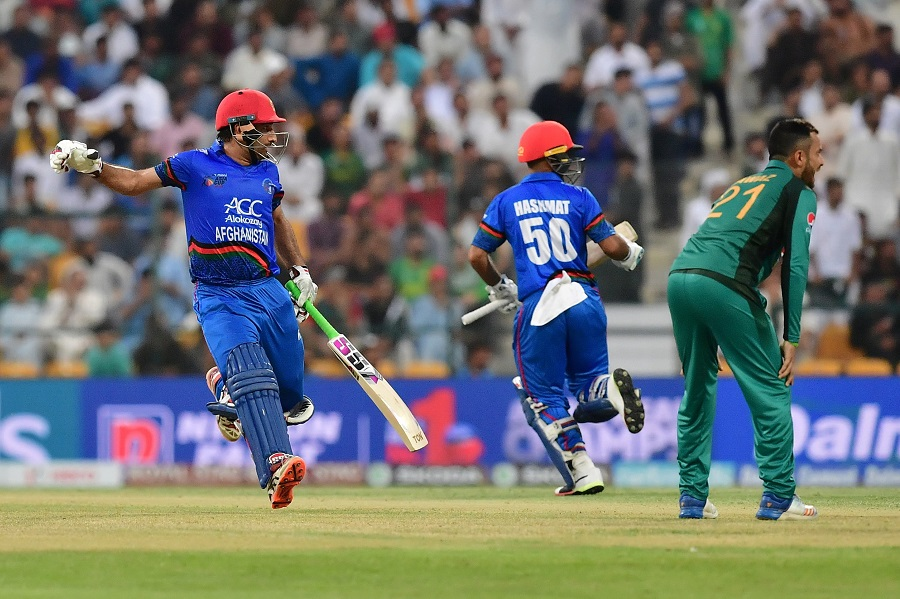 Afghanistan team captain and batsman Mohammad Asghar (L) runs between the wickets. PHOTO: AFP