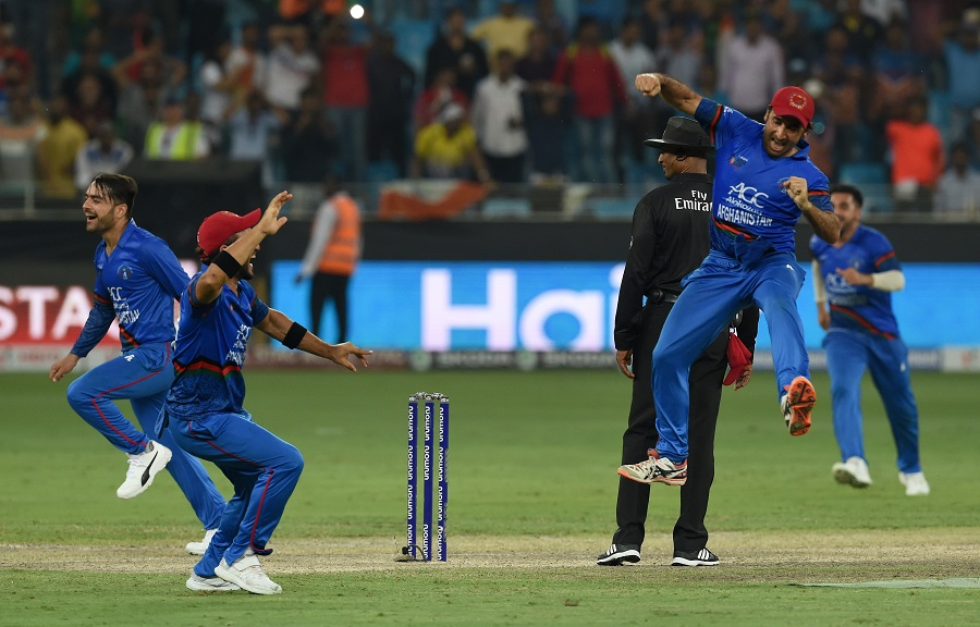 Afghanistan Cricket captain Asghar Afghan (R) celebrates with teammate after the match. PHOTO: AFP