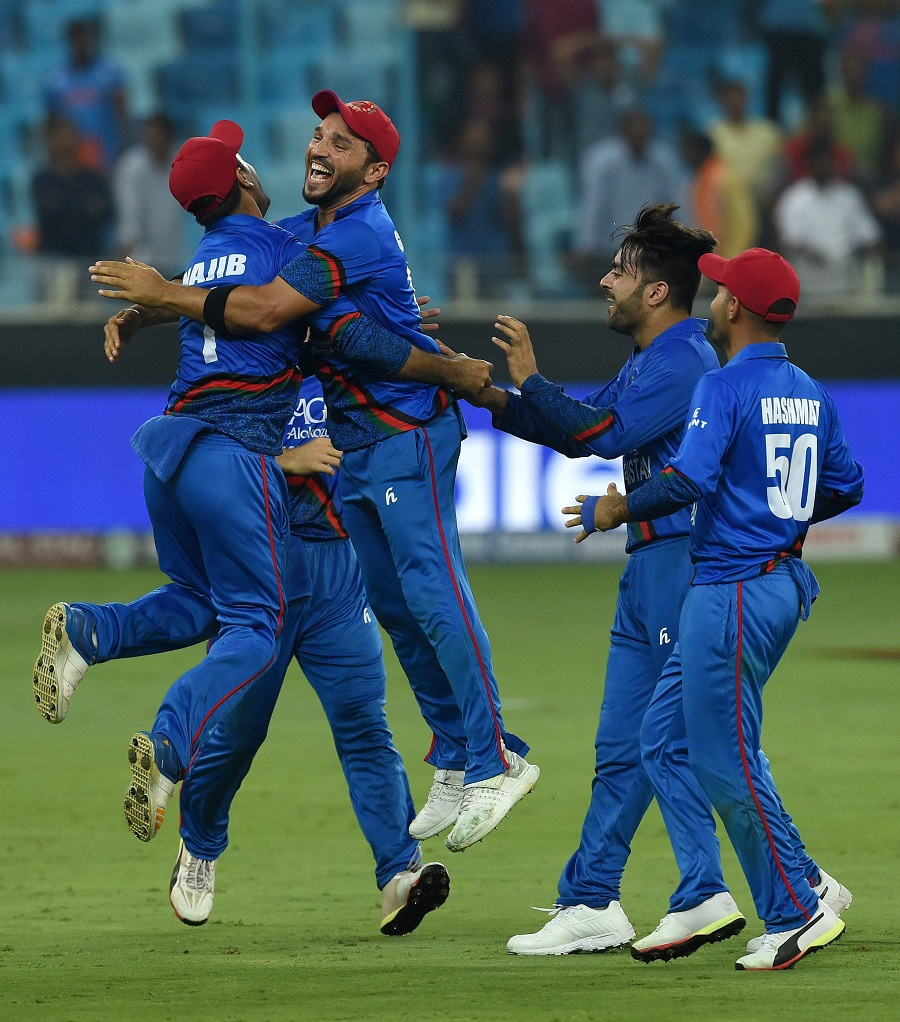 Afghan cricketer Rashid Khan (2R) celebrates with teammate after the match. PHOTO: AFP