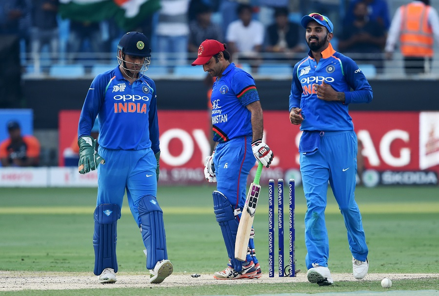 Afghanistan cricket captain Asghar Afghan (C) reacts after being dismissed by Indian cricketer Kuldeep Yadav as Indian wicketkeeper Mahendra Singh Dhoni (L) and cricketer Lokesh Rahul look