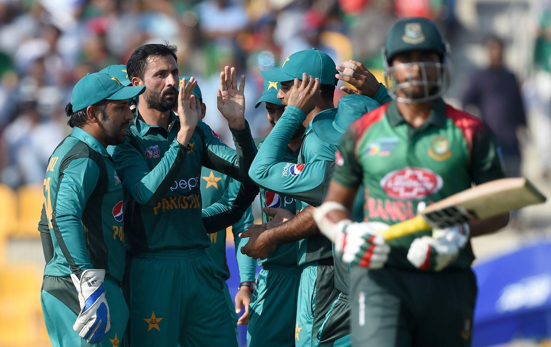 Pakistan cricketer Junaid Khan (2L) celebrates with teammates after he dismissed Bangladesh batsman Soumya Sarkar (R)