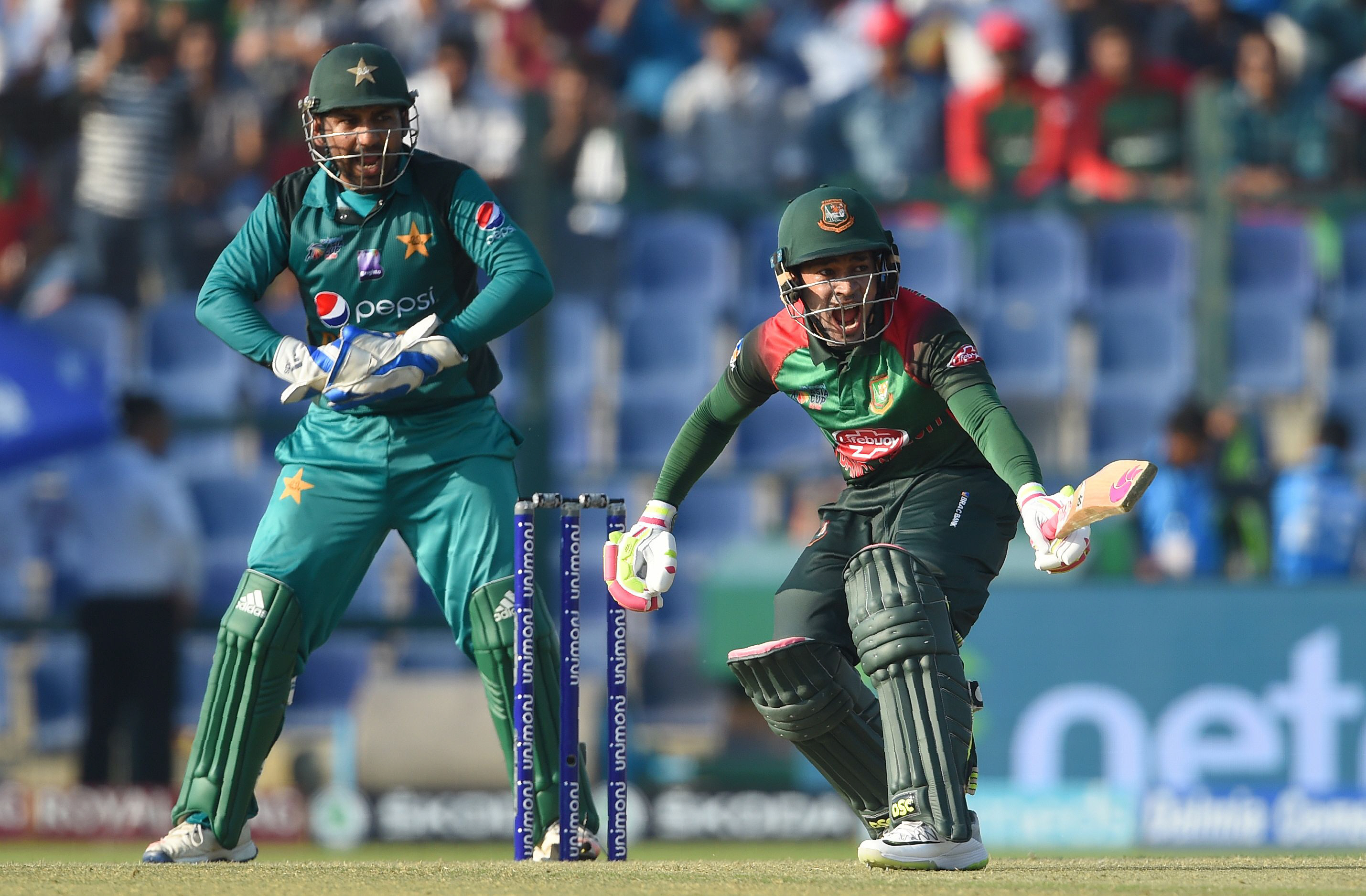 Bangladesh batsman Mushfiqur Rahim (R) reacts as Pakistan captain Sarfraz Ahmed (L) looks on during the one day international (ODI) Asia Cup cricket match