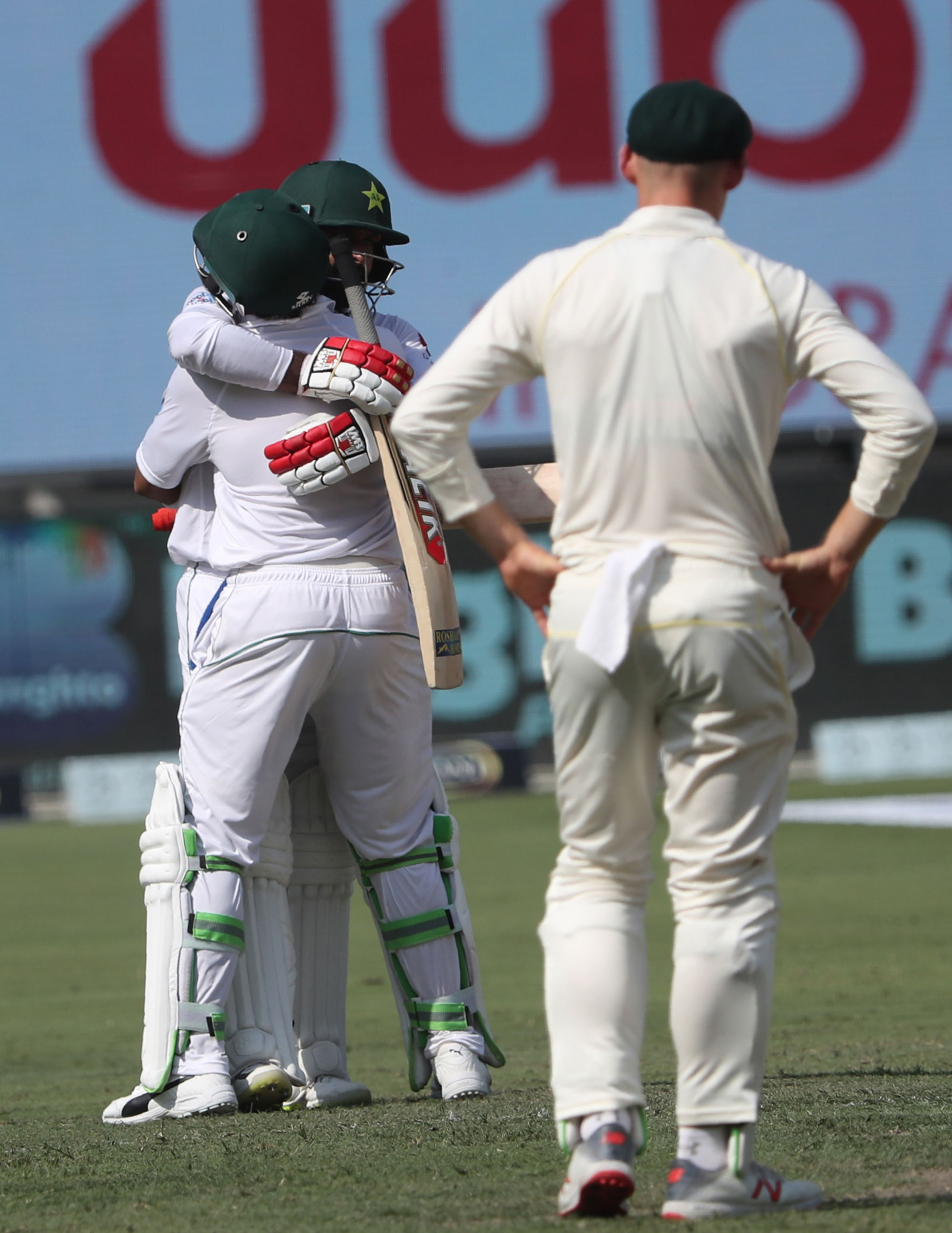1.	Pakistan cricketer Mohammad Hafeez of Pakistan (L) celebrates his century on day one of the 1st test cricket match between Australia and Pakistan at the Dubai International Cricket Stadium in Dubai on October 7, 2018. - Pakistan openers Mohammad Hafeez