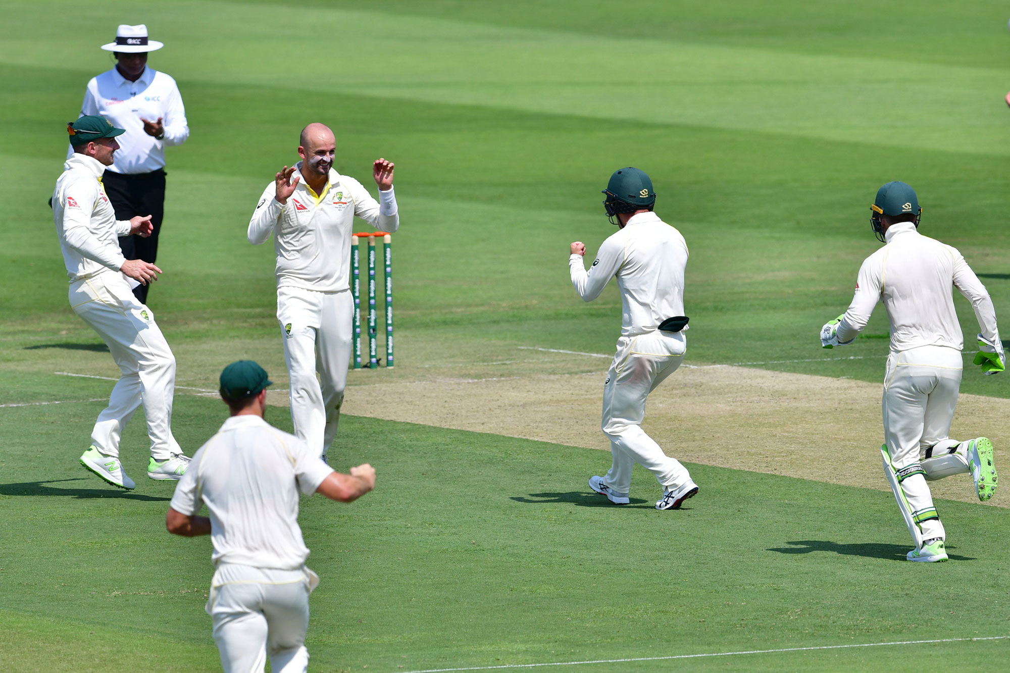 Australia cricketer Nathan Lyon (2nd L) celebrates after he dismissed Pakistan cricketer Asad Shafiq during day one of the second Test cricket match in the series between Australia and Pakistan at the Abu Dhabi Cricket Stadium in Abu Dhabi on October 16,