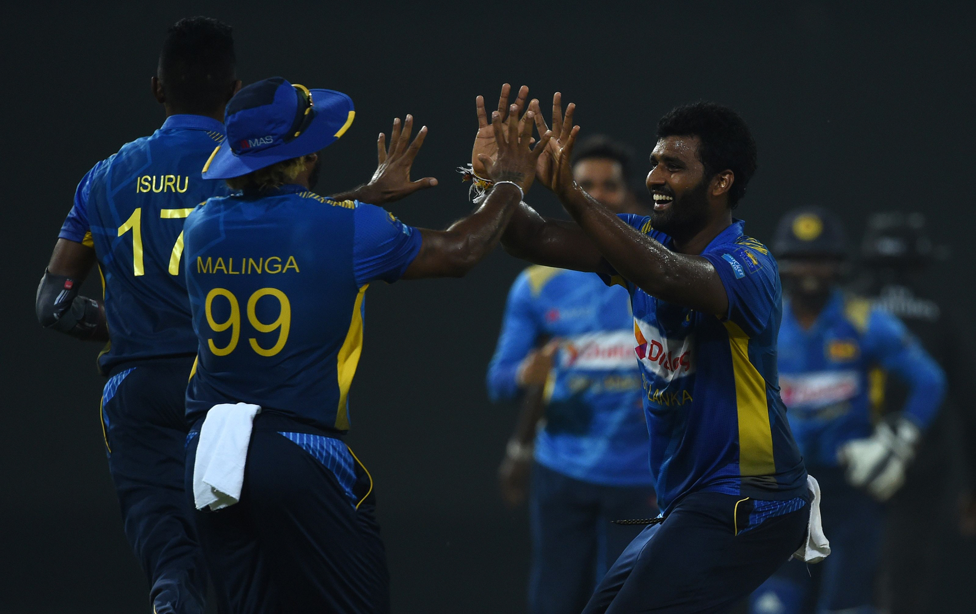 Sri Lankan cricket captain Thisara Perera (R) celebrates with teammates after he dismissed England cricket captain Eoin Morgan during the international Twenty20 cricket match between Sri Lanka and England at the R. Peremadasa Stadium in Colombo on October