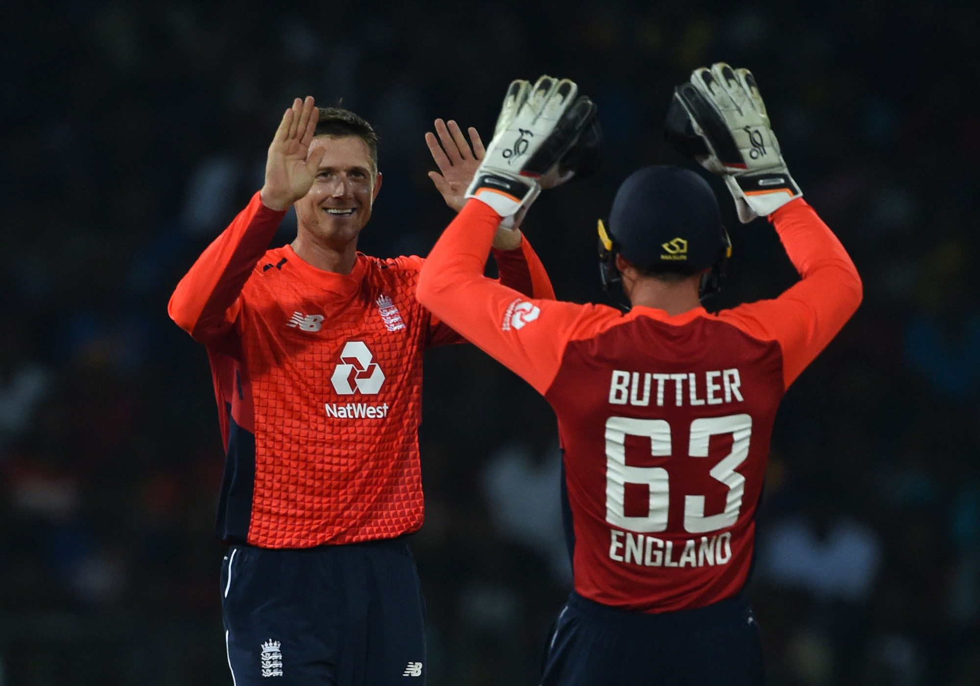England's bowler Joe Denly (L) celebrates with England's wicketkeeper Jos Buttler after he dismissed Sri Lankan cricketer Niroshan Dickwella during the Twenty20 International cricket match between Sri Lanka and England at the R. Premadasa Stadium in Colom