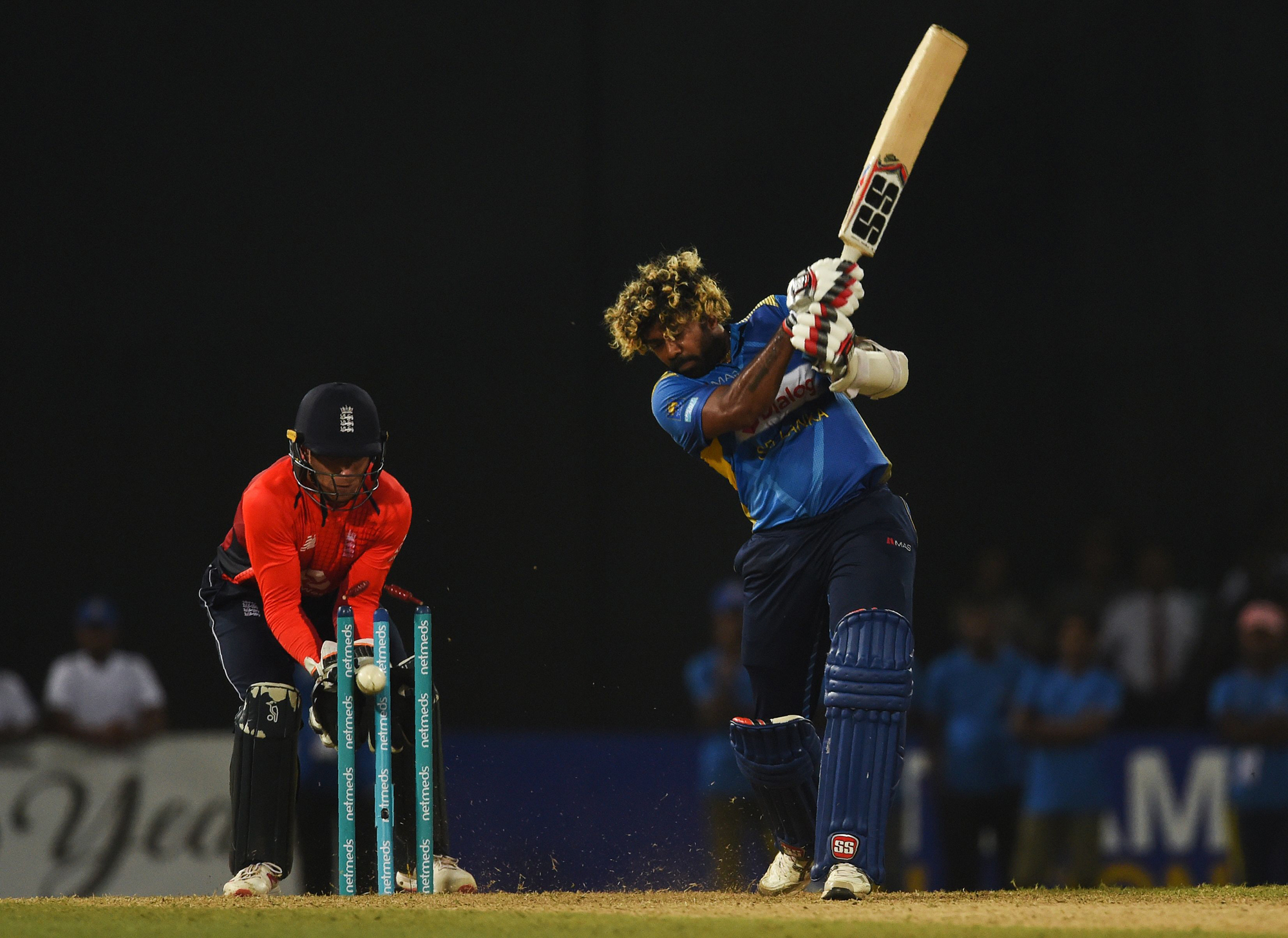 Sri Lankan cricketer Lasith Malinga (R) is dismissed as England wicket keeper Jos Buttler (L) looks on during the Twenty20 International cricket match between Sri Lanka and England at the R. Premadasa Stadium in Colombo on October 27, 2018. (Photo by ISHA