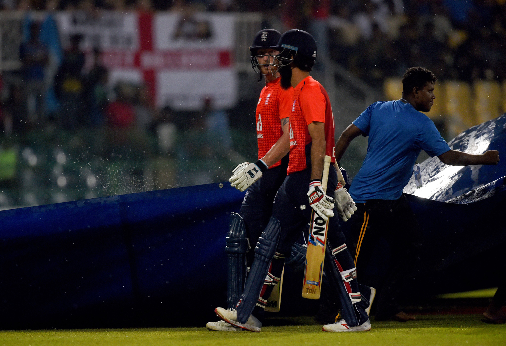 England cricketer Ben Stokes (L) and Moeen Ali leave the ground after rain showers have stop the play during the international Twenty20 cricket match between Sri Lanka and England at the R. Peremadasa Stadium in Colombo on October 27, 2018. (Photo by ISHA