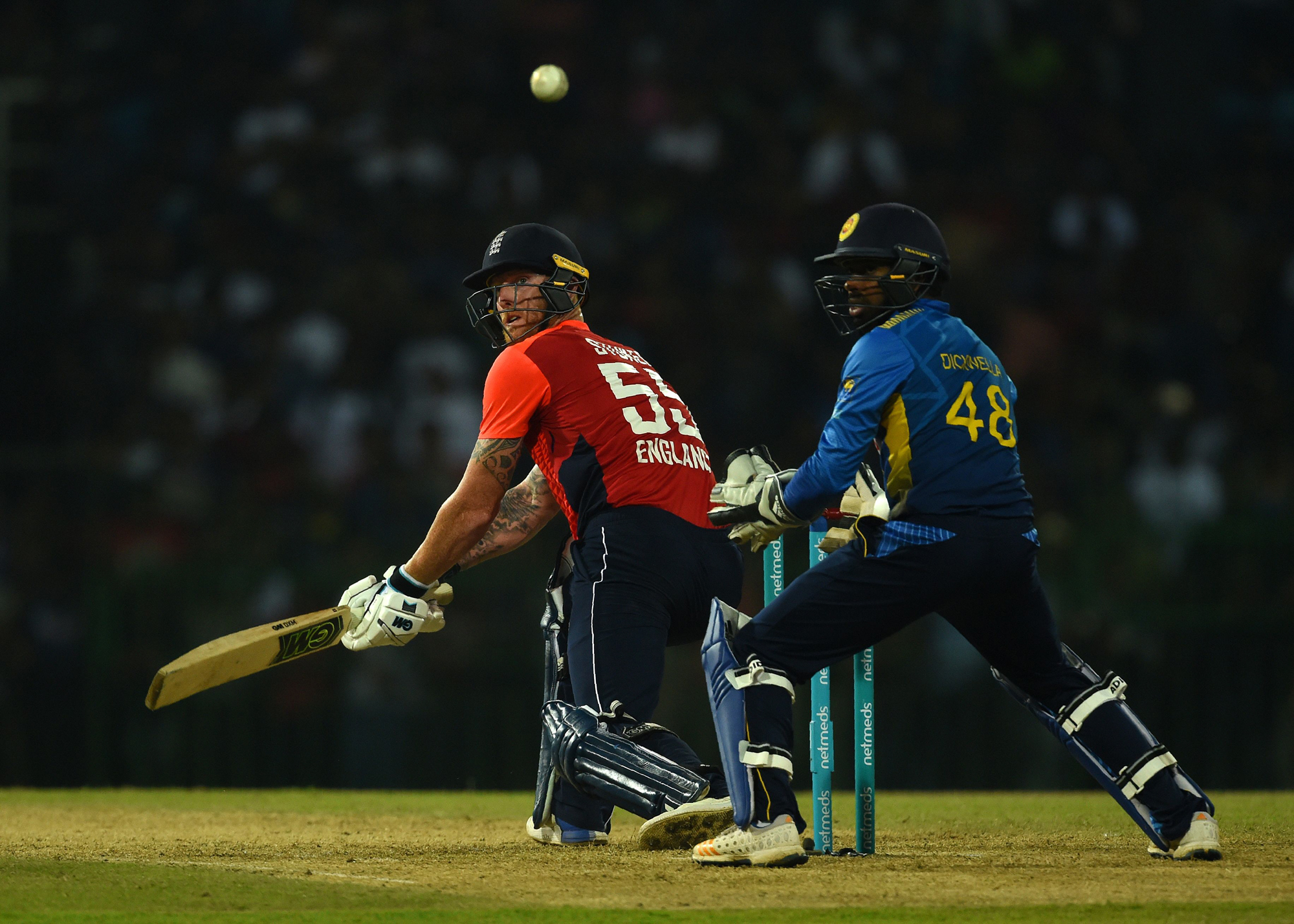 England cricketer Ben Stokes (L) plays a shot as Sri Lankan wicketkeeper Niroshan Dickwella (R) looks on during the international Twenty20 cricket match between Sri Lanka and England at the R. Peremadasa Stadium in Colombo on October 27, 2018. (Photo by I