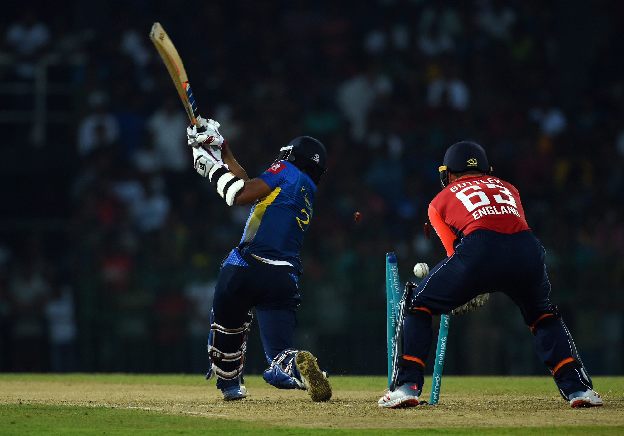 Sri Lankan cricketer Kusal Mendis (L) is dismissed by England's bowler Joe Denly (not pictured) as England's wicket keeper Jos Buttler looks on (R) during the Twenty20 International cricket match between Sri Lanka and England at the R. Premadasa Stadium i