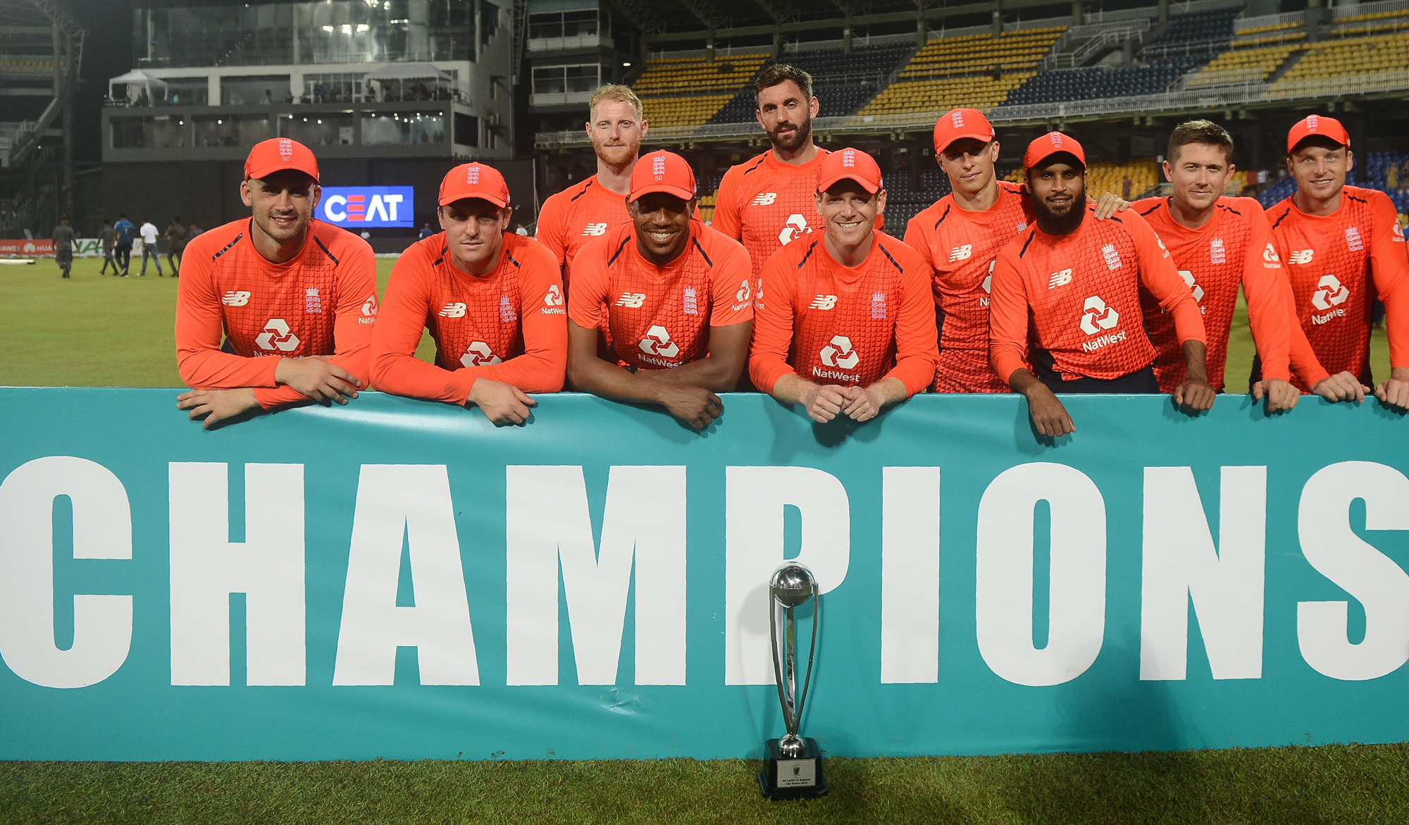 England cricket captain Eoin Morgan (C) and team poses with the winners trophy after winning the Twenty20 International cricket match between Sri Lanka and England at the R Peremadasa Stadium in Colombo on October 27, 2018. (Photo by ISHARA S. KODIKARA /