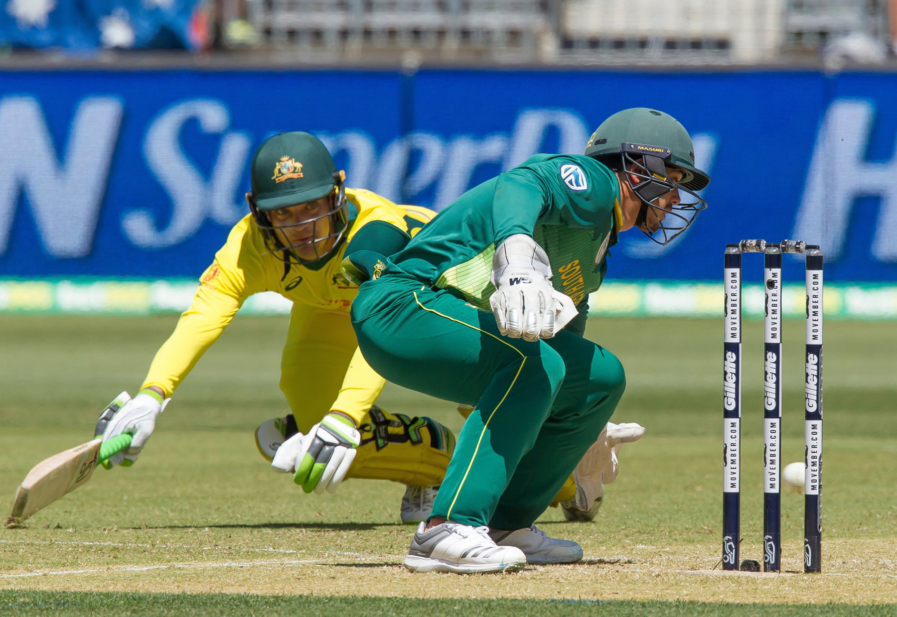 Australia's Alex Carey dives into his crease to avoid a run-out as South Africa's wicketkeeper Quinton de Kock watches during the first one-day international (ODI) cricket match between South Africa and Australia at the Optus Stadium in Perth on November