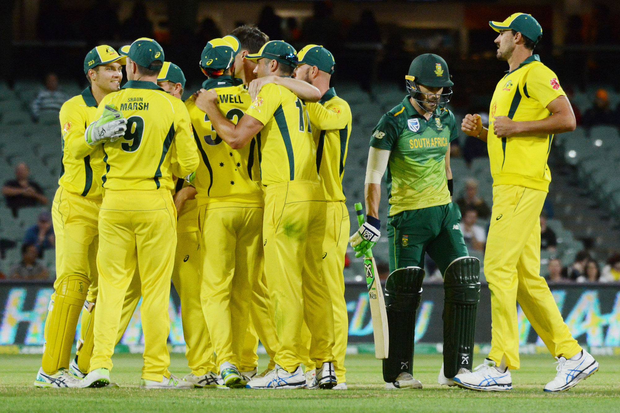 Australia's teammates congratulate Josh Hazlewood (C) after taking the wicket of South Africa's Reeza Hendricks during the second one day international cricket match between Australia and South Africa at the Adelaide Oval in Adelaide on November 9, 2018.