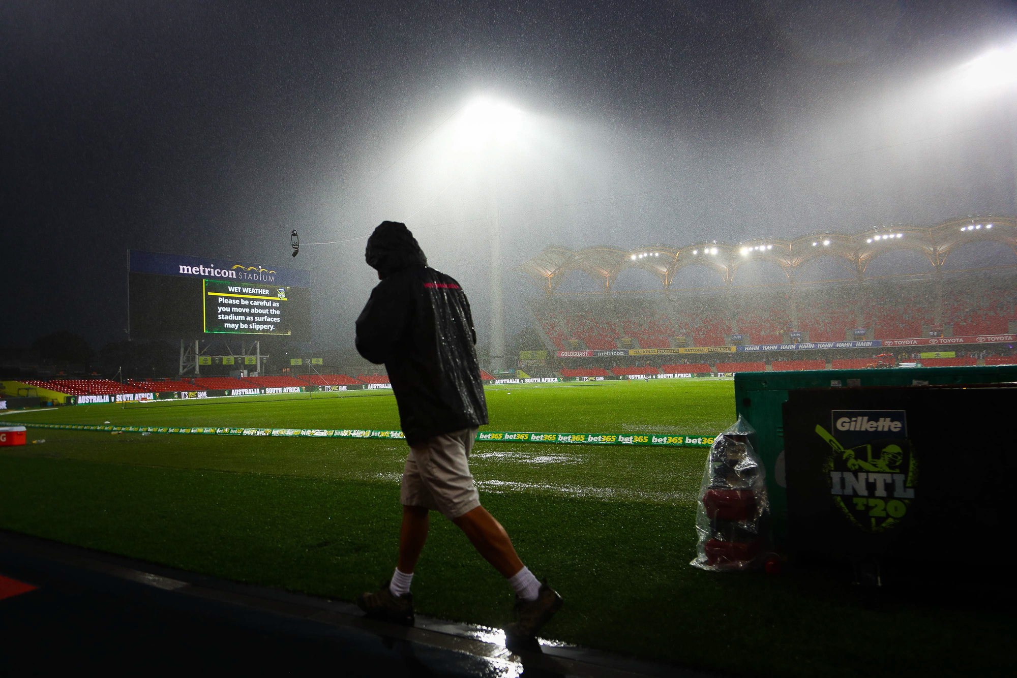 A ground attendant runs off the field during heavy rain that delayed the T20 international cricket match between Australia and South Africa at Metricon Stadium on the Gold Coast on November 17, 2018. (Photo by Patrick HAMILTON / AFP) / -- IMAGE RESTRICTED