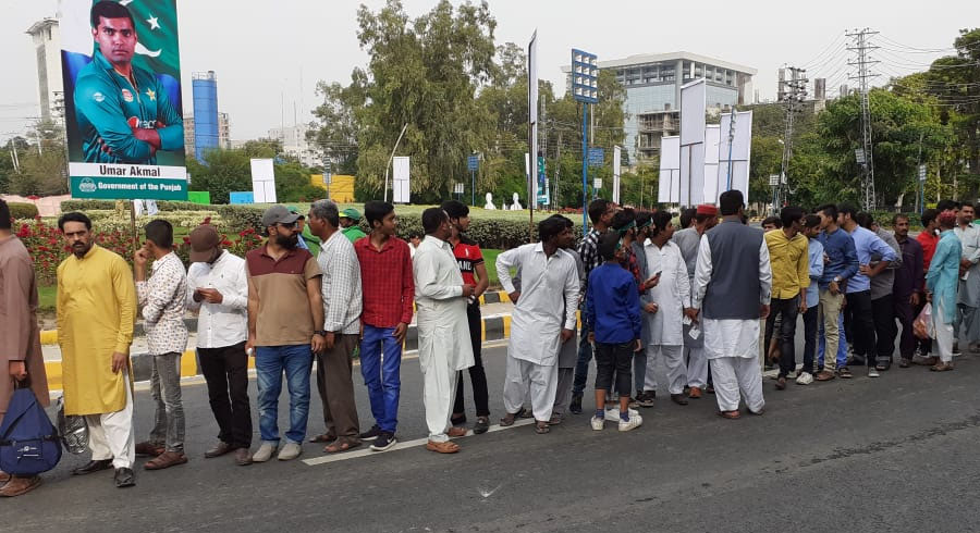 Fans queue outside the Gaddafi Stadium